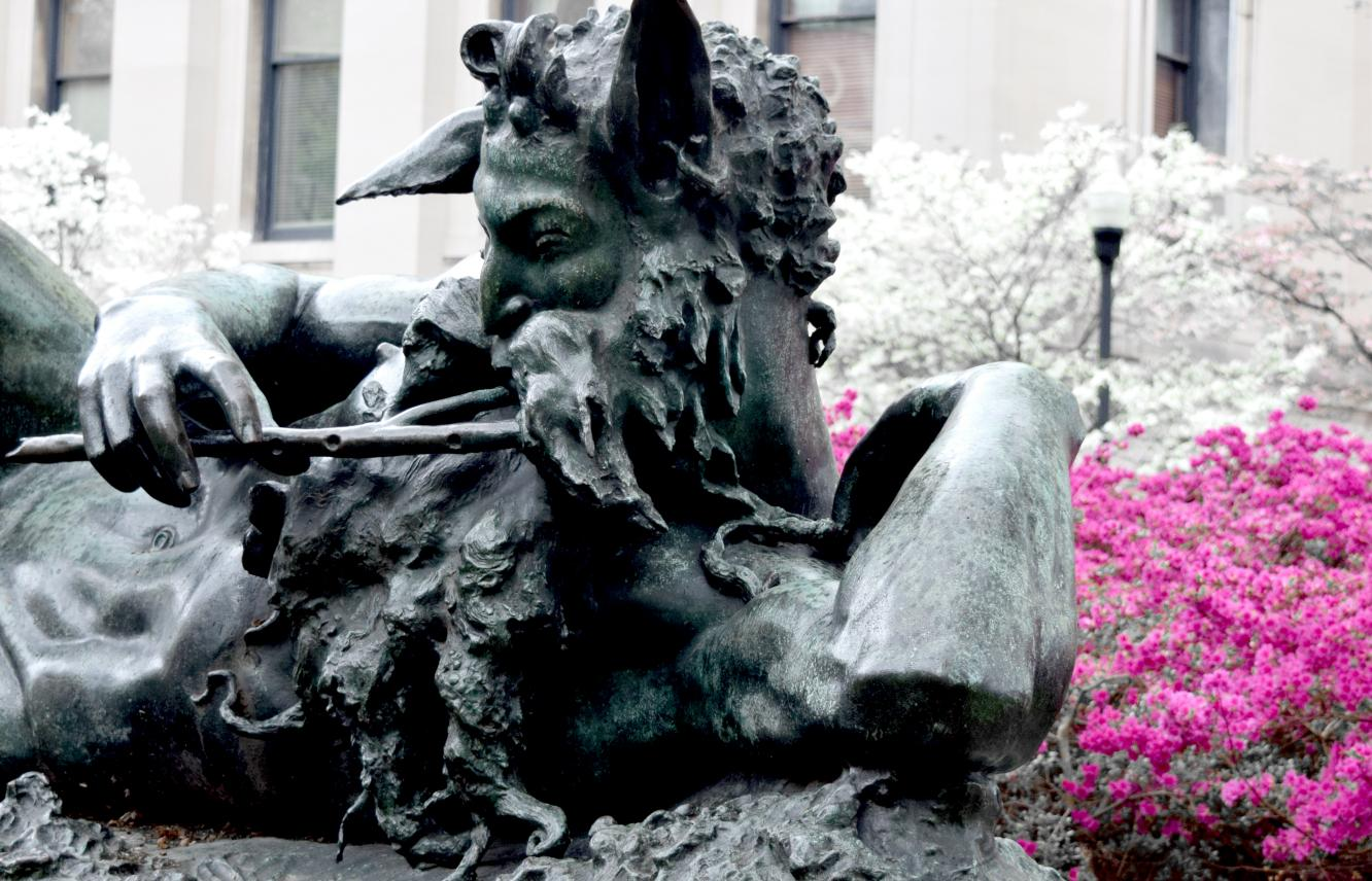 Pan statue with shrubs in bloom